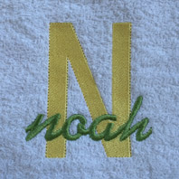 embroidered name in cursive on baby blanket with blue trim