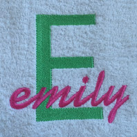 embroidered name in cursive on baby blanket with pink trim